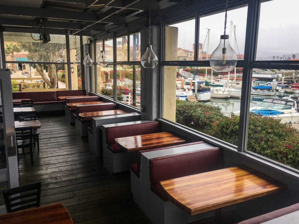 booths inside fratelli's pizza and brew with watrerfront view of boats