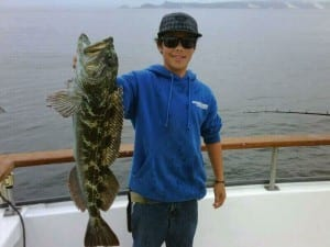 A boy showing off his catch of the day, which is nearly as big as he is himself!