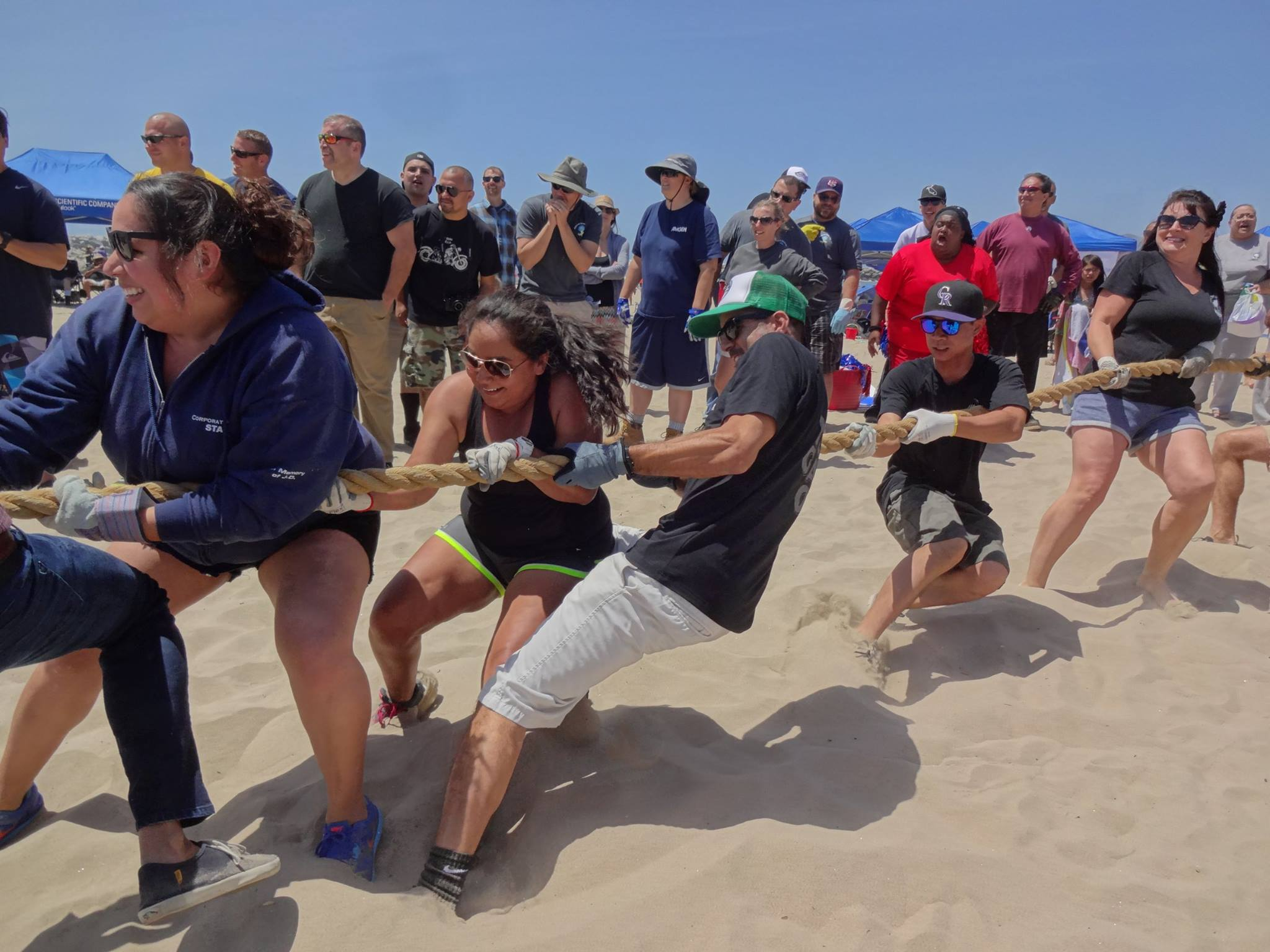 A team playing tug-o-war, digging their feet into the white sand and pulling their end of the rope with all of their strength