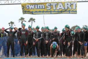 A group of triathletes gearing up and getting ready for the swimming portion of their competition