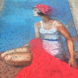 A street chalk portrait of a women sitting on the sand