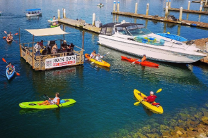 "The floating ""Rock the Dock"" stage in Ventura Harbor surrounded by event goers in kayaks"