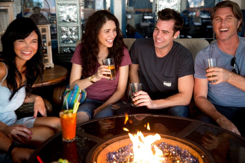 Good laughs make a good time, people enjoying some drinks and friendly company around a nice, warm, beautiful fire seaside