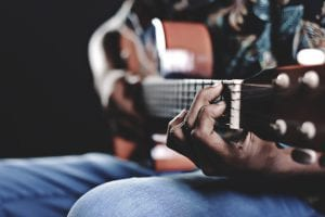 Strong hands holding a guitar and holding the strings while strumming a tune
