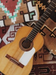 Guitar sitting on top of a small handful of geometric patterned blankets