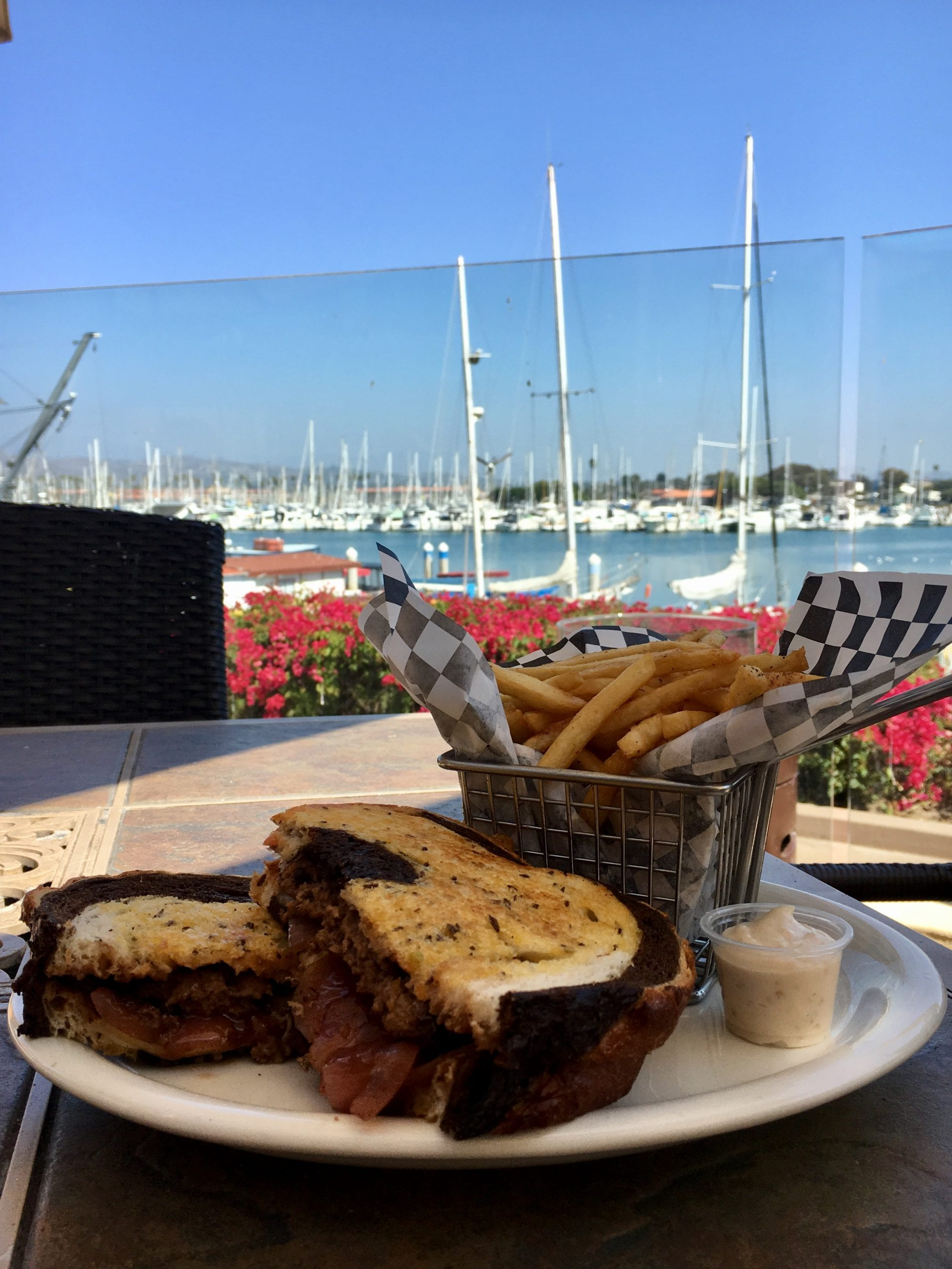 a beautifully made grilled cheese sandwich on rye bread stuffed with gooey goodness with crisp French fries in front of the gorgeous backdrop of Ventura Harbor Village