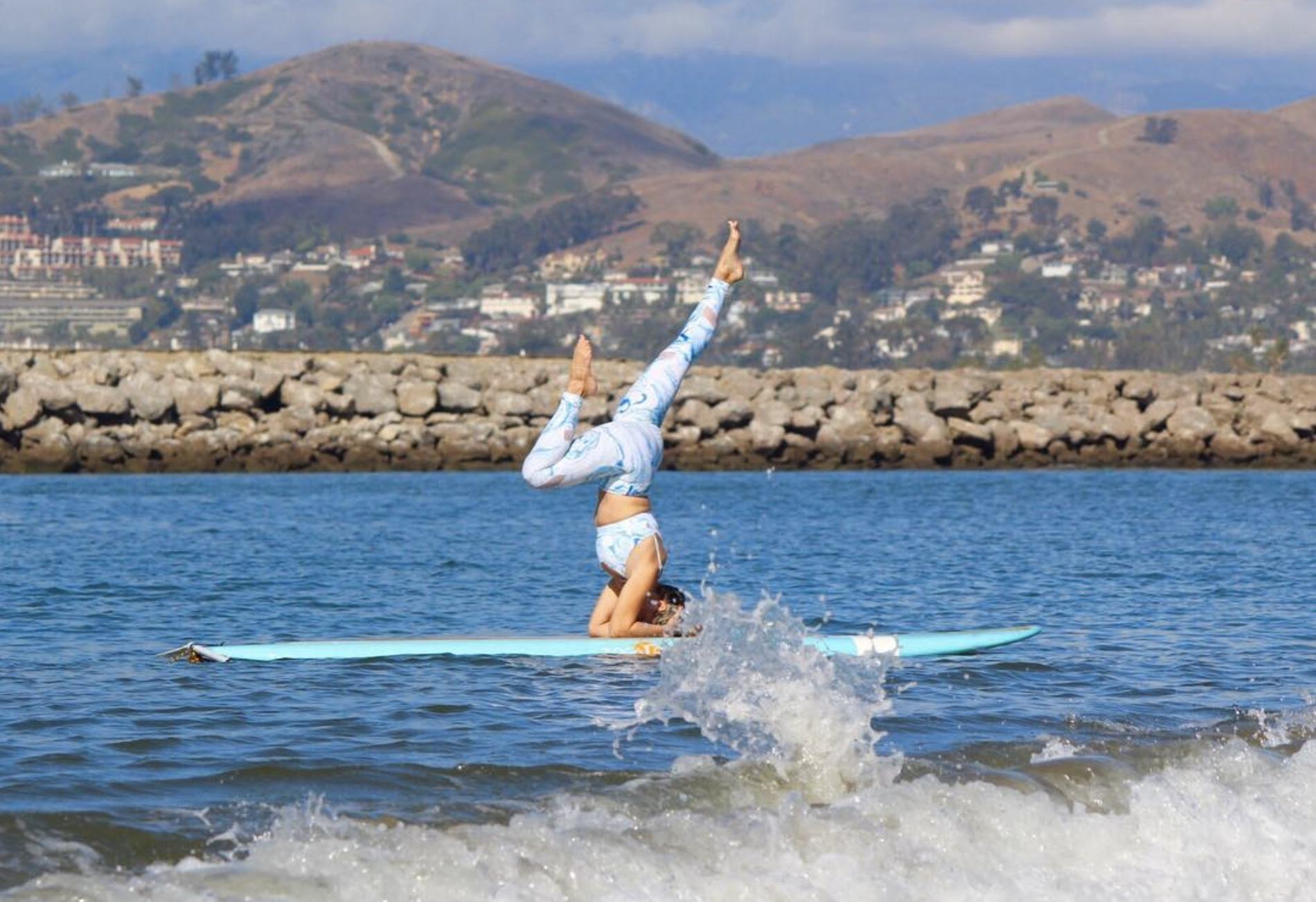woman holding an upside down yoga pose on a surfboard amongst the rocking of the waves under her board