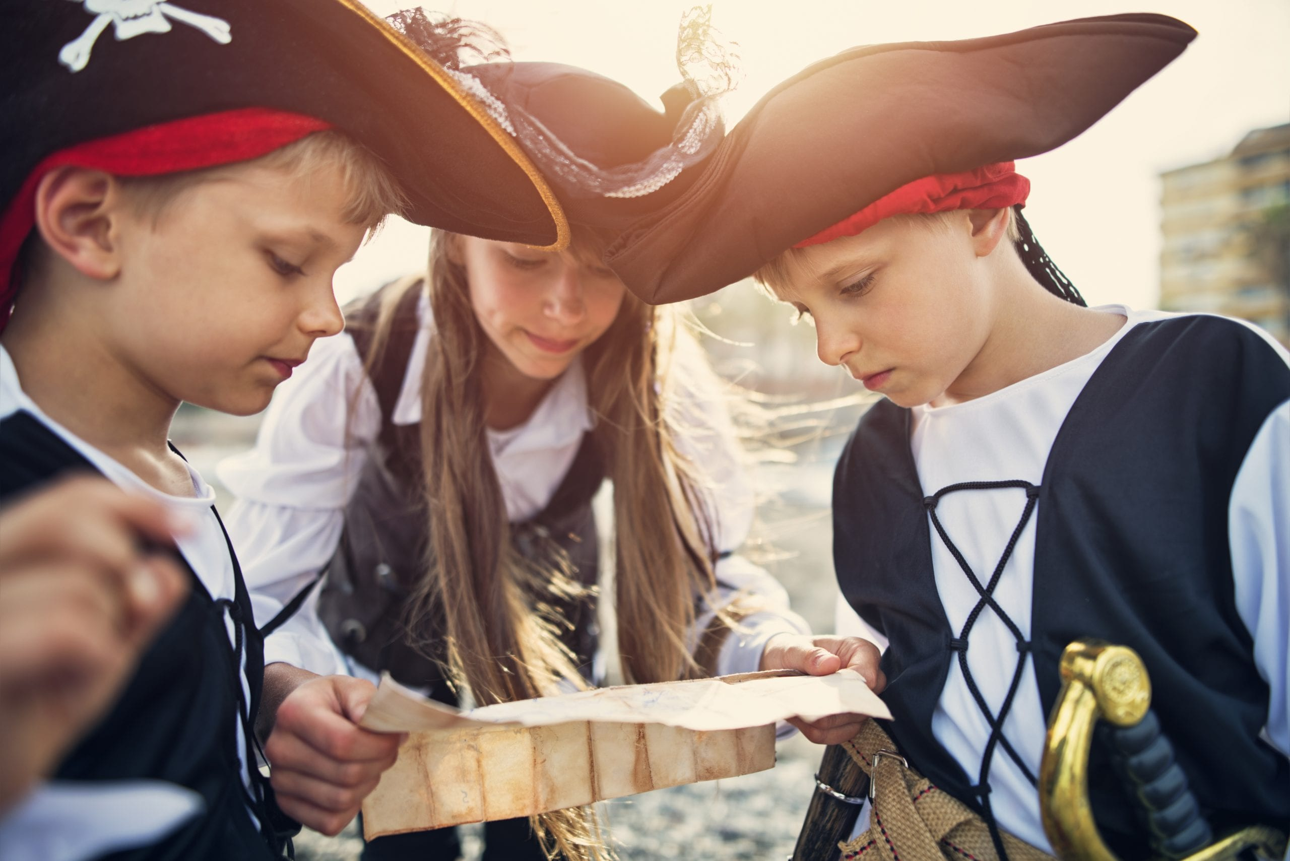 Three little pirates, a girl aged 11 and two boys aged 7 are playing pirates on the beach. They are trying to read ancient treasure map that leads to ... a treasure.