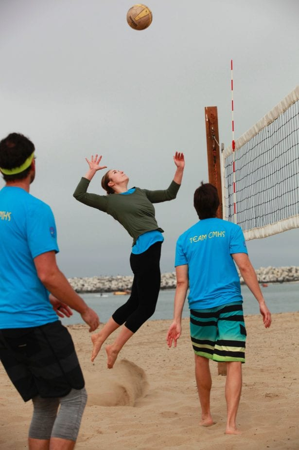 woman spiking a volleyball over the net