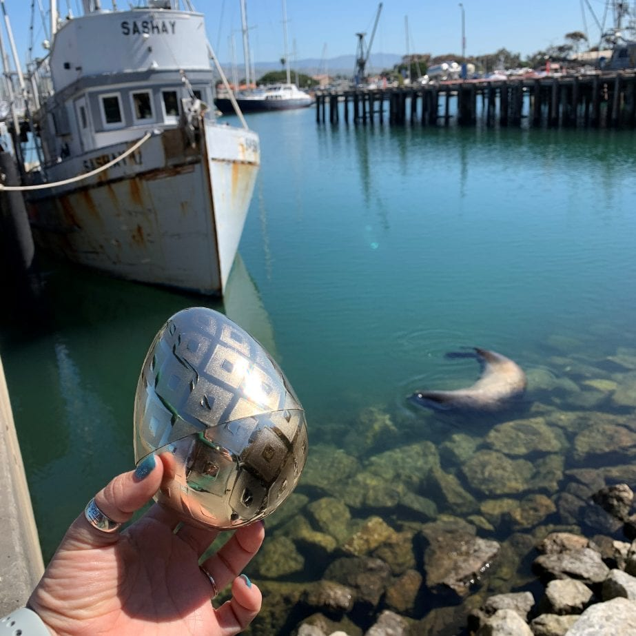 Person holding silver egg in front of a boat