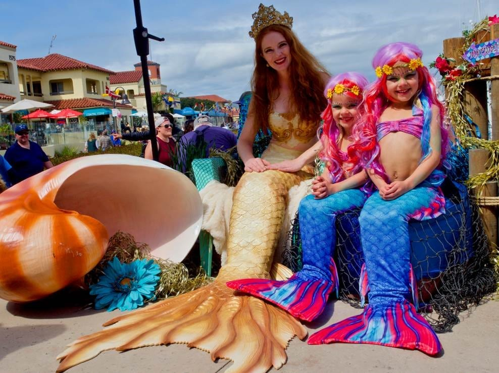 adult mermaid with mermaid children sitting and smiling