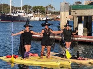 three women dressed as witches posing while about to go paddle boarding