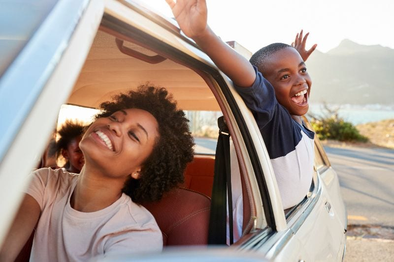 two people sticking their heads out the window of a car feeling the wind