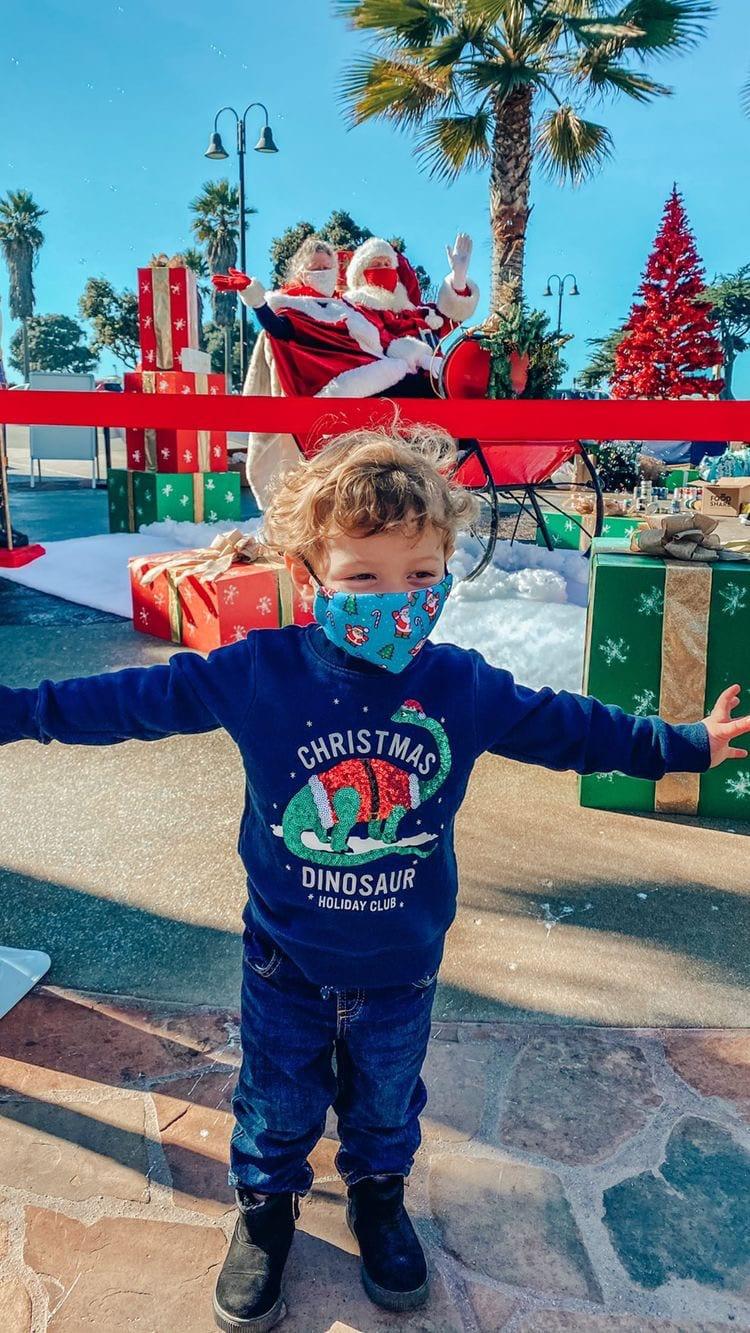 happy child in mask in front of santa