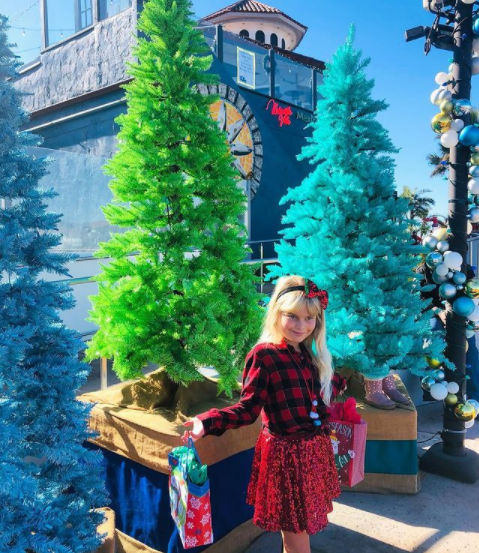 little girl with shopping bags in front of festive colorful trees in ventura harbor