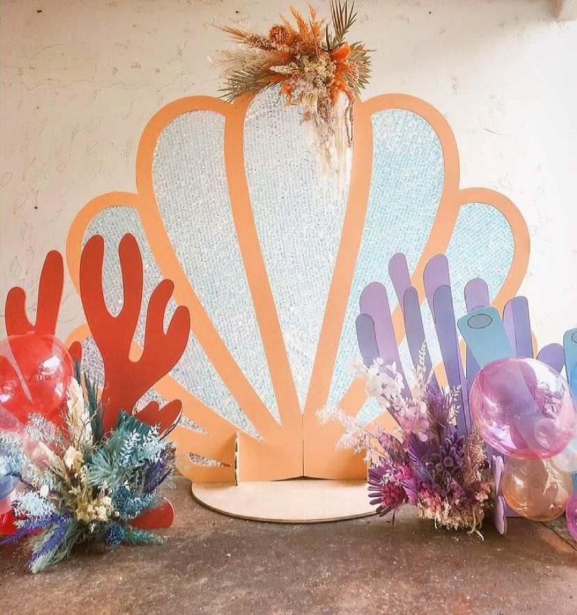 large clam shell structure with coral and dried colorful florals