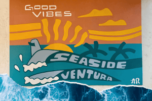 A mural with surf board, waves, sun, palm trees and good vibes seaside