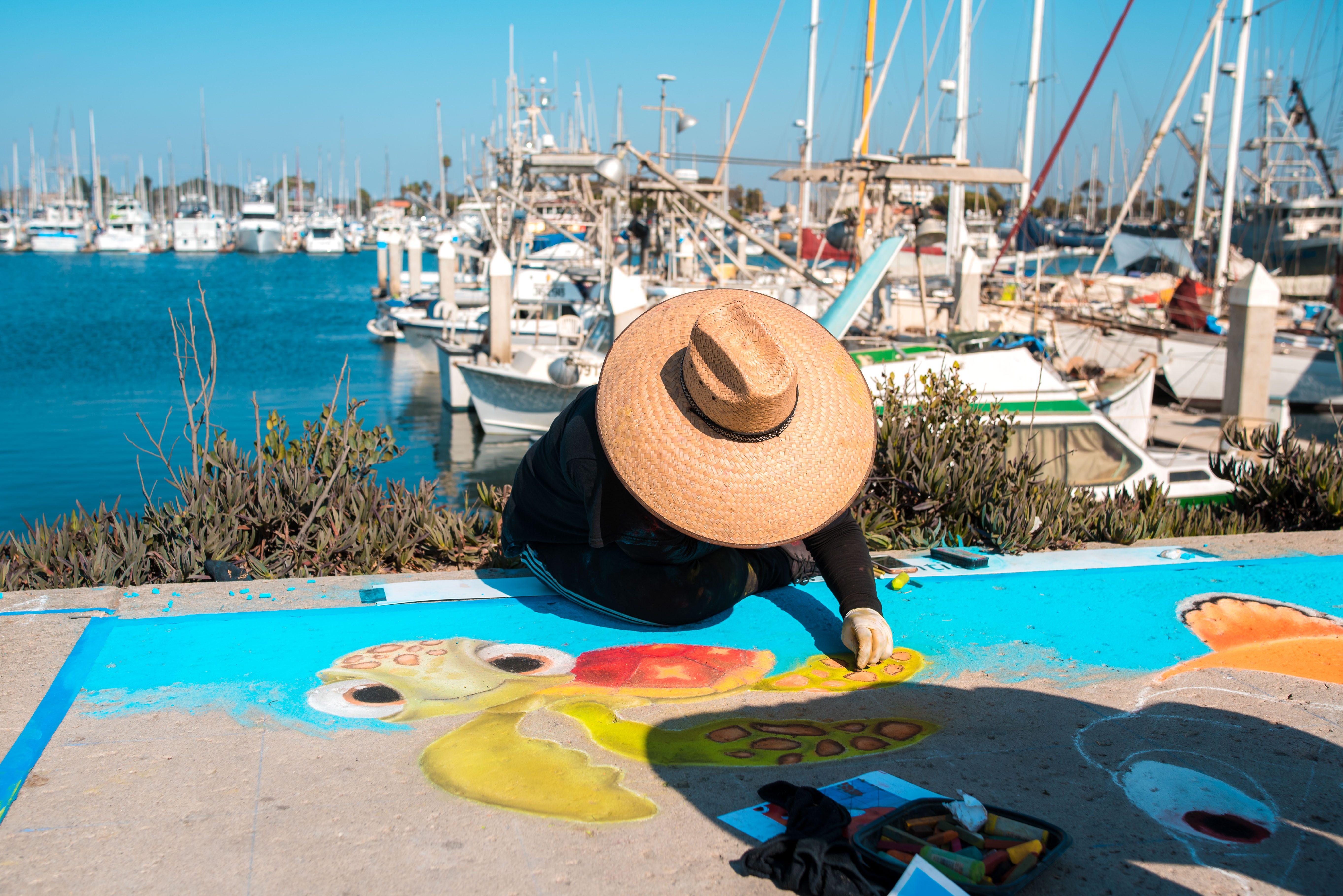 chalk artist at work on ventura harbors waterfront promenade