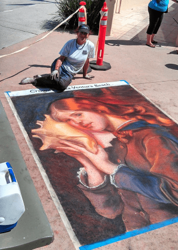 Lorelle Miller with chalk painting of a red head girl holding a shell to her ear