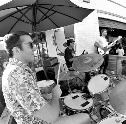 drummer in foreground and other band members in background covered by umbrella
