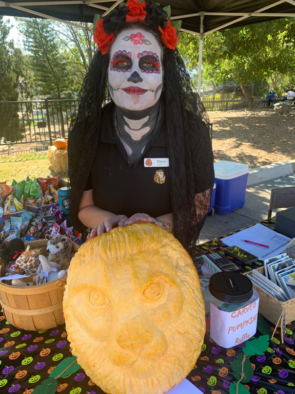 Dawn reiling in dia de los muertos costume with a large pumpkin carving