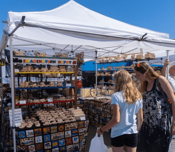 mother and daughter looking at vendor art