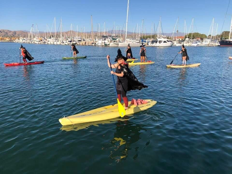 ladies in witch costumes on paddle boards